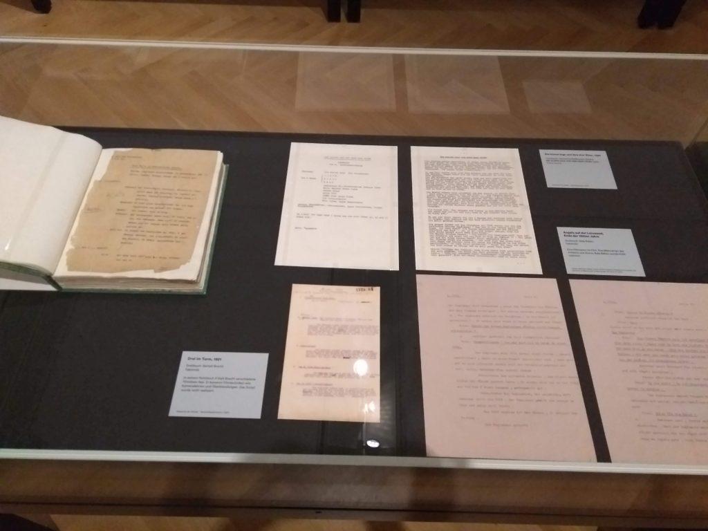 Eine Tischvitrine mit mehreren Textdokumenten.