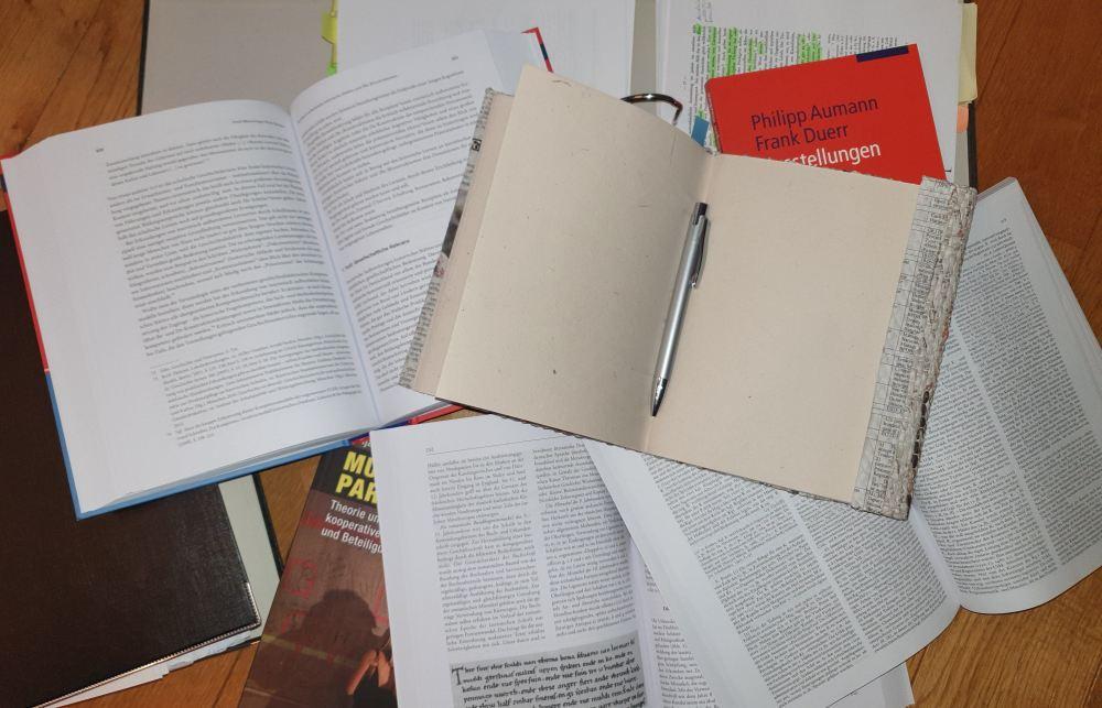 Bücherstapel mit aufgeschlagenen Büchern